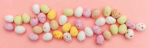 E Αυγά σοκολάτας καραμελών Πάσχας και jellybean γλυκά που απομονώνονται στο καθιερώνον τη μόδα ρόδινο υπόβαθρο κρητιδογραφιών r στοκ εικόνες