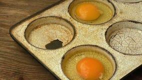 Αυγά στο παλαιό βαρέων καθηκόντων τηγανίζοντας τηγάνι χάλυβα που απομονώνεται στο ξύλινο υπόβαθρο φιλμ μικρού μήκους