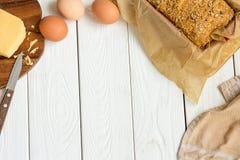 Αυγά, τυρί και σπιτικό ελεύθερο γλυκό ψωμί γλουτένης στο πιάτο ψησίματος σε ένα ελαφρύ άσπρο ξύλινο υπόβαθρο Αγροτικό κουζίνα ή α στοκ εικόνα