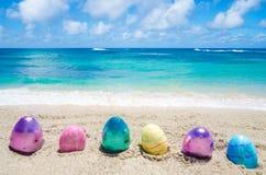 Αυγά χρώματος Πάσχας στην παραλία κοντά στον ωκεανό στοκ εικόνες