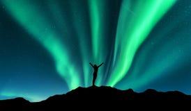 Αυγή και σκιαγραφία της μόνιμης γυναίκας με αυξημένος επάνω στα όπλα στο βουνό στη Νορβηγία Αυγή Borealis στοκ εικόνες
