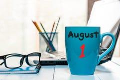 1 Αυγούστου ημέρα του μήνα 1, φλυτζάνι καφέ πρωινού με το ημερολόγιο στο υπόβαθρο επιχειρησιακών εργασιακών χώρων νεολαίες ενηλίκ Στοκ φωτογραφίες με δικαίωμα ελεύθερης χρήσης