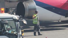 15 Αυγούστου 2018, Μόσχα, Ρωσία - ο υπάλληλος αερολιμένων σε μια αντανακλαστική φανέλλα διατάζει τη μετακίνηση ενός φορτηγού υπηρ φιλμ μικρού μήκους
