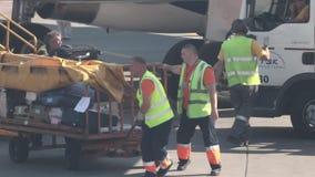 15 Αυγούστου 2018, Μόσχα, Ρωσία - το προσωπικό αερολιμένων στις αντανακλαστικές φανέλλες κινεί το καροτσάκι με το φορτίο αποσκευώ απόθεμα βίντεο