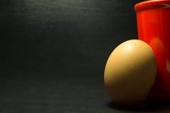 Αυγό και κόκκινο γυαλί στο μαύρο υπόβαθρο σχεδίων Στοκ Εικόνα