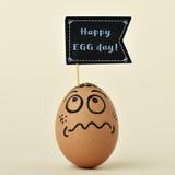 Αυγό με μια πινακίδα με την ευτυχή ημέρα αυγών κειμένων Στοκ Φωτογραφία