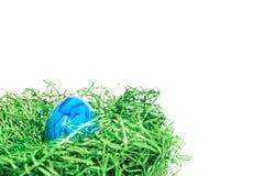 Αυγό Πάσχας σε μια φωλιά Πάσχας φιαγμένη από πράσινη χλόη και κίτρινο υπόβαθρο Στοκ Φωτογραφίες