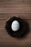 Αυγό Πάσχας στη φωλιά στα ξύλινα γενικά έξοδα Στοκ Φωτογραφίες