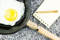 Αυγό σε ένα τηγανίζοντας τηγάνι και ένα σημειωματάριο στο γκρίζο αμμοχάλικο στοκ εικόνες