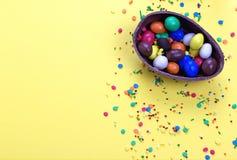 Αυγό σοκολάτας Πάσχας με τη ζωηρόχρωμη έκρηξη των καραμελών και των γλυκών στο κίτρινο χρωματισμένο υπόβαθρο Στοκ εικόνα με δικαίωμα ελεύθερης χρήσης