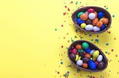 Αυγό σοκολάτας Πάσχας με τη ζωηρόχρωμη έκρηξη των καραμελών και των γλυκών στο κίτρινο χρωματισμένο υπόβαθρο Στοκ φωτογραφία με δικαίωμα ελεύθερης χρήσης