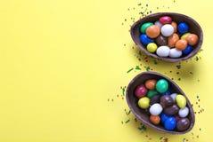 Αυγό σοκολάτας Πάσχας με τη ζωηρόχρωμη έκρηξη των καραμελών και των γλυκών στο κίτρινο χρωματισμένο υπόβαθρο Στοκ Εικόνα