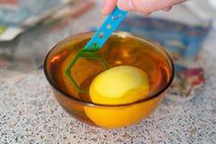Αυγό στο κίτρινο κύπελλο με το χρώμα Διακόσμηση αυγών Πάσχας στοκ φωτογραφία