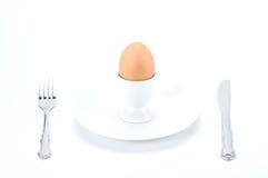 Αυγό στο φλυτζάνι στο πιάτο με το δίκρανο και το μαχαίρι Στοκ Εικόνα