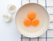 Αυγό τρία yorks με το κοχύλι αυγών στο τραπεζομάντιλο Στοκ φωτογραφία με δικαίωμα ελεύθερης χρήσης