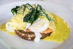 Αυγό Benedict στο καφετί σπιτικό ψωμί, που ολοκληρώνει με το πράσινο σπανάκι και την κίτρινη σάλτσα κρέμας Στοκ Εικόνα