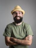Αυθόρμητα σκληρά γελώντας γενειοφόρο άτομο που φορά το καπέλο αχύρου που εξετάζει τη κάμερα Στοκ Εικόνα