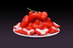 Αυξήθηκε μήλο, κόκκινα φρούτα στο άσπρο πιάτο, που απομονώθηκε στο μαύρο υπόβαθρο Στοκ εικόνα με δικαίωμα ελεύθερης χρήσης