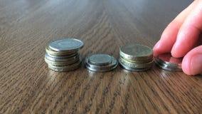 Αυξανόμενη έννοια χρημάτων Τεθειμένα χέρι νομίσματα στον πίνακα κλείστε επάνω απόθεμα βίντεο