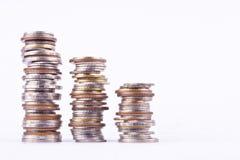 Αυξανόμενος τη γραφική παράσταση χρημάτων σε μια σειρά του νομίσματος και το σωρό των νομισμάτων λουτρών συσσωρεύστε στην άσπρη ε Στοκ Εικόνες
