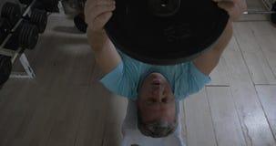 Αυξημένο άτομο σε μια γυμναστική που βρίσκεται στον πάγκο και τη βλασφημία αυξήσεων από πάνω απόθεμα βίντεο