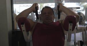 Αυξημένο άτομο στη γυμναστική που εκτελεί τις ασκήσεις στα ανώτερα ABS απόθεμα βίντεο