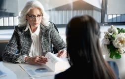 Αυστηρή ηλικιωμένη γυναίκα που συνεργάζεται με το συνάδελφό της Στοκ Εικόνες