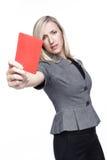 Αυστηρή νέα γυναίκα που παρουσιάζει κόκκινη κάρτα Στοκ Εικόνες