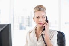 Αυστηρή νέα ξανθή επιχειρηματίας που απαντά στο τηλέφωνο Στοκ Φωτογραφία
