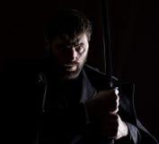 Αυστηρός 0 επιχειρηματίας σε ένα παλτό μαλλιού με το ξίφος στο σκοτεινό υπόβαθρο Στοκ φωτογραφία με δικαίωμα ελεύθερης χρήσης