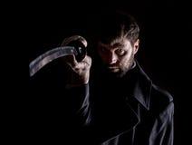 Αυστηρός 0 επιχειρηματίας σε ένα παλτό μαλλιού με το ξίφος στο σκοτεινό υπόβαθρο Στοκ Εικόνες