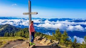 Αυστρία - κορίτσι που κλίνει στο σταυρό στην κορυφή ενός βουνού, άποψη στην κοιλάδα στοκ φωτογραφία με δικαίωμα ελεύθερης χρήσης