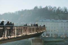 Αυστρία, Σάλτζμπουργκ, την 1η Ιανουαρίου 2017: Η για τους πεζούς γέφυρα Μότσαρτ ` s συνδέει τις παλαιές και νέες πόλεις Οι πεζοί  Στοκ Εικόνες