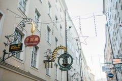 Αυστρία, Σάλτζμπουργκ, την 1η Ιανουαρίου 2017: Σημάδια διαφήμισης των καταστημάτων στην οδό Getreidegasse Μια γραφική οδός στον π Στοκ φωτογραφία με δικαίωμα ελεύθερης χρήσης