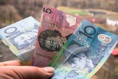 Αυστραλιανά τραπεζογραμμάτια στο χέρι ατόμων με τη εικονική παράσταση πόλης στο υπόβαθρο στοκ εικόνες