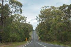 Αυστραλιανός δρόμος εσωτερικών κατά μήκος του θάμνου, δάσος με το κίτρινο οδικό σημάδι στοκ εικόνα