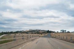 Αυστραλιανός εσωτερικός, δρόμος επαρχίας με το αγροτικό υπόβαθρο στοκ φωτογραφίες