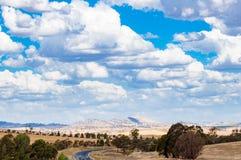 Αυστραλιανό τοπίο εσωτερικών με τους απόμακρους λόφους και το δρόμο στοκ εικόνες