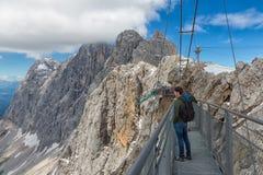 Αυστριακά βουνά Dachstein με τους οδοιπόρους που περνούν μια γέφυρα σχοινιών χάλυβα Στοκ Εικόνα