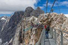 Αυστριακά βουνά Dachstein με τους οδοιπόρους που περνούν μια γέφυρα σχοινιών χάλυβα Στοκ εικόνες με δικαίωμα ελεύθερης χρήσης