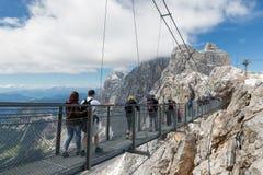 Αυστριακά βουνά Dachstein με τους οδοιπόρους που περνούν ένα σχοινί skywalk Στοκ εικόνα με δικαίωμα ελεύθερης χρήσης