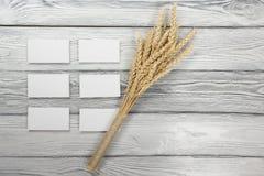 Αυτιά σίτου στον ξύλινο πίνακα με τις κενές επαγγελματικές κάρτες Sheaf του σίτου πέρα από το ξύλινο υπόβαθρο Έννοια συγκομιδών Στοκ Φωτογραφία