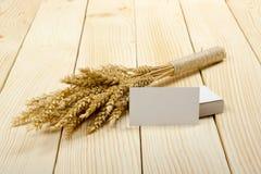 Αυτιά σίτου στον ξύλινο πίνακα με τις κενές επαγγελματικές κάρτες Sheaf του σίτου πέρα από το ξύλινο υπόβαθρο Έννοια συγκομιδών Στοκ Εικόνες