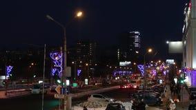 Αυτοκίνητα και άνθρωποι που πηγαίνουν στην οδό στη χειμερινή νύχτα απόθεμα βίντεο