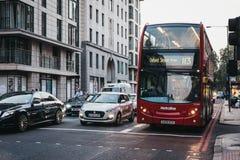 Αυτοκίνητα και ένα κόκκινο διπλό λεωφορείο αριθμός 113 καταστρωμάτων προς την Οξφόρδη Stree στοκ εικόνα με δικαίωμα ελεύθερης χρήσης