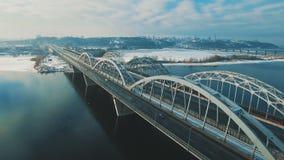 Αυτοκίνητα και κινήσεις τραίνων σε μια γέφυρα πέρα από ένα παγωμένο μήκος σε πόδηα κηφήνων ποταμών εναέριο φιλμ μικρού μήκους