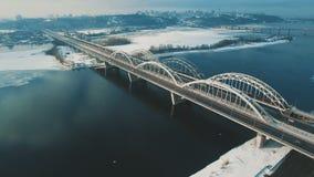 Αυτοκίνητα και κινήσεις τραίνων σε μια γέφυρα πέρα από ένα παγωμένο μήκος σε πόδηα κηφήνων ποταμών εναέριο απόθεμα βίντεο