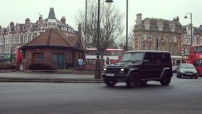 Αυτοκίνητα και κόκκινα διώροφα λεωφορεία που κυκλοφορούν στη διασταύρωση κυκλικής κυκλοφορίας στο Hill Broadway, Λονδίνο, Αγγλία  φιλμ μικρού μήκους