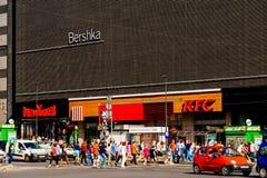 Αυτοκίνητα που περιμένουν στο φωτεινό σηματοδότη τους πεζούς για να διασχίσουν την οδό Στοκ Φωτογραφία