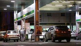 Αυτοκίνητα σε έναν ανεφοδιάζοντας σε καύσιμα σταθμό απόθεμα βίντεο
